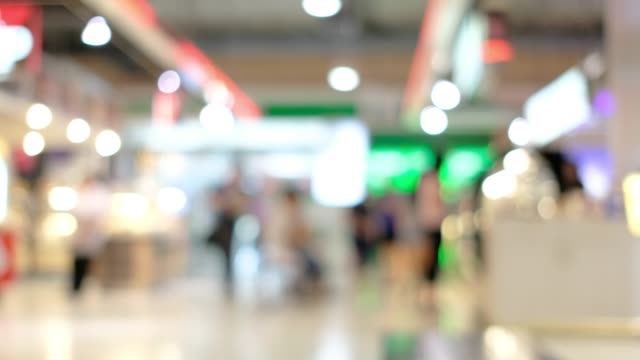 blurred background of shopping mall with customer walking in front of  store with bokeh light. blurred background of shopping mall with customer walking in front of  store with bokeh light. department store stock videos & royalty-free footage