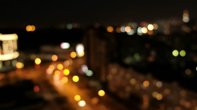 Blurred bokeh light spots on black background. Blurred bokeh light spots on black background. Lights of the night city and street. image focus technique stock videos & royalty-free footage