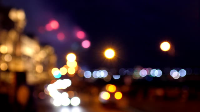 Blurred bright fireworks explosions and sparks at night sky over Saint Petersburg. Series of fire rockets expanding to glowing flowers in bokeh lights. 3840x2160 video