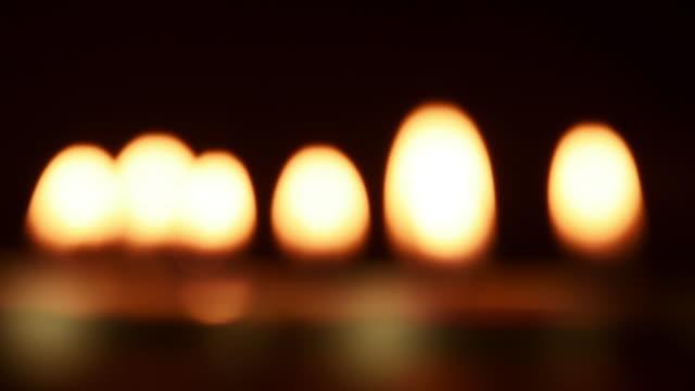 verschwommene kerzenlichter im schwarzen hintergrund - mahnwachen stock-videos und b-roll-filmmaterial