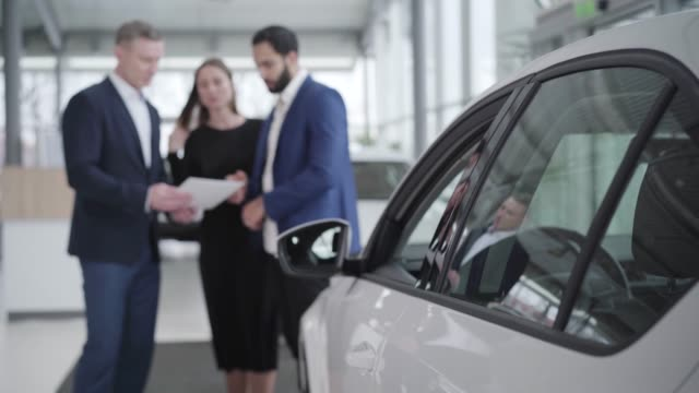 Blurred car dealer showing booklet to multiracial couple in showroom. Young Middle Eastern man and Caucasian woman choosing automobile in dealership. Business, success, lifestyle, industry. Blurred car dealer showing booklet to multiracial couple in showroom. Young Middle Eastern man and Caucasian woman choosing automobile in dealership. Business, success, lifestyle, industry. car salesperson stock videos & royalty-free footage