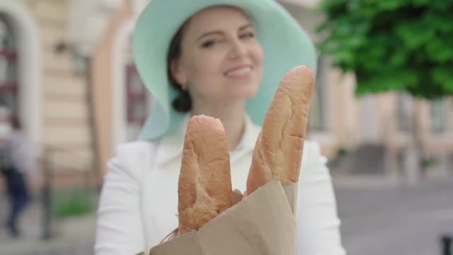 verschwommene kaukasische frau streckt frische leckere baguettes zur kamera und lächelt. porträt der eleganten positiven dame posiert mit bäckerei auf sonnigen stadtstraße im freien. - einzelne frau über 30 stock-videos und b-roll-filmmaterial
