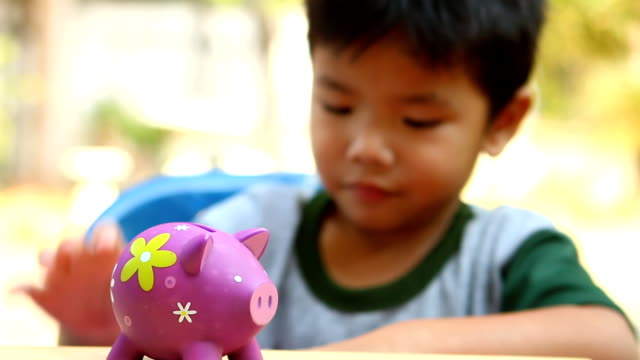 blurred child dropping coins in to piggy bank - salvadanaio video stock e b–roll