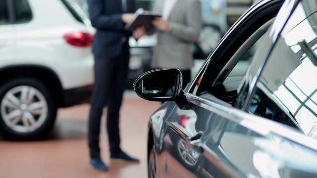 Blurred customer and seller behind a car