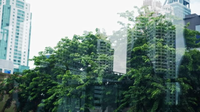vídeos de stock e filmes b-roll de blurred double exposure style business people walking pass with urban city landscape background - green city