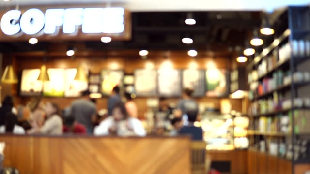 Blurred footage of coffee shop with people drinking coffee. 4K video with defocused effect.