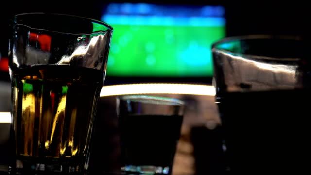 Verschwommenes Bild der Sport-Bar mit TV und Getränken im Vordergrund – Video