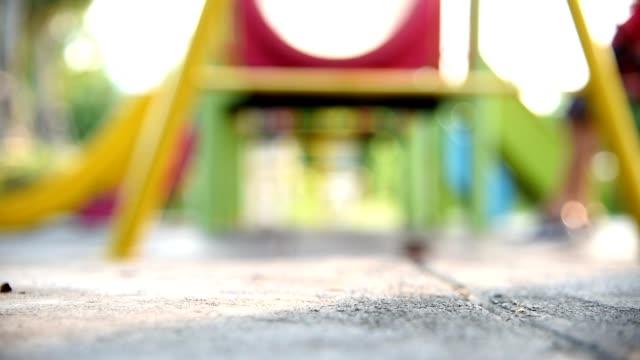 verschwommene kinder schaukeln an bunten spielplatz spielen. - kinderspielplatz stock-videos und b-roll-filmmaterial