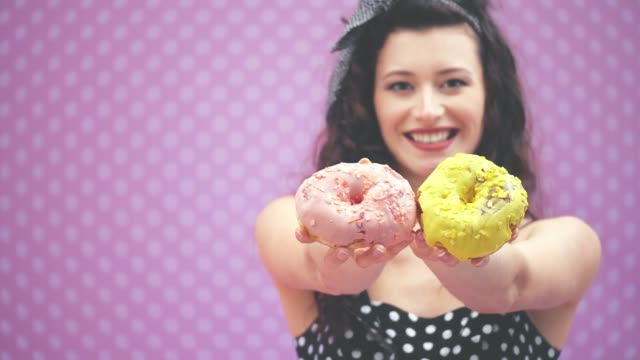 blurred lovely young curly girl standing, extending two yummy doughnuts in pink and yellow icing to the camera. focus on the doughnuts on the forefront. - paczka sukienka filmów i materiałów b-roll