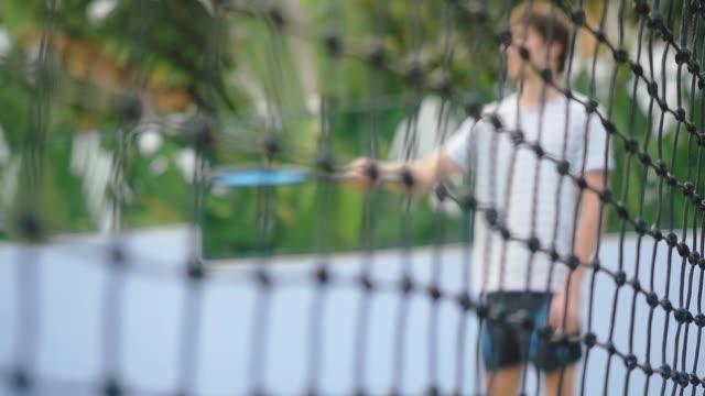 blurred man beats the tennis ball from the racket on focused grid on the foreground. slow motion. 1920x1080 - rozgrzewka filmów i materiałów b-roll