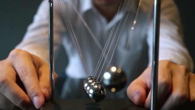 vídeos de stock e filmes b-roll de blurred man pulling ball of newton cradle - continuidade