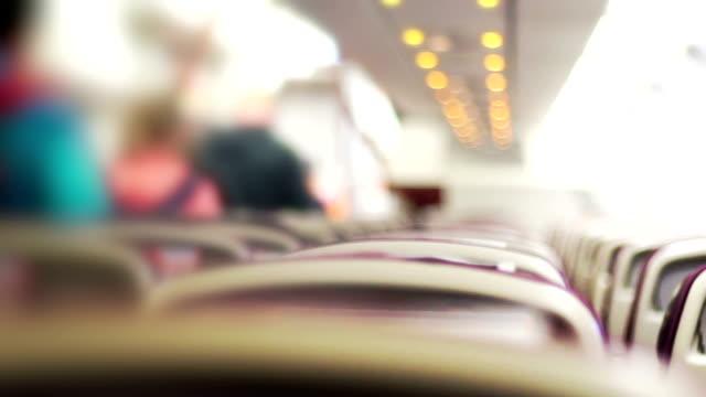 통로 걸어 승객과 비행기의 인테리어의 흐리게 동작입니다. - airplane seat 스톡 비디오 및 b-롤 화면
