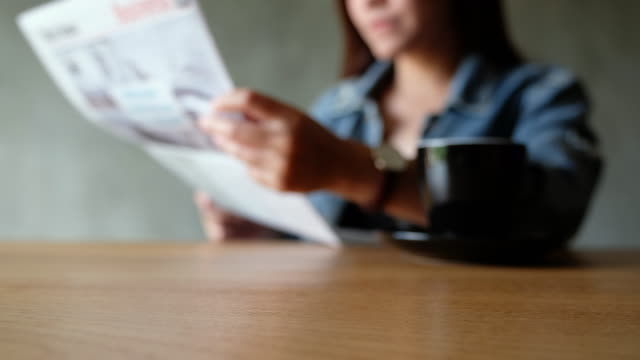 Blurred of a woman reading newspaper with coffee cup on the table