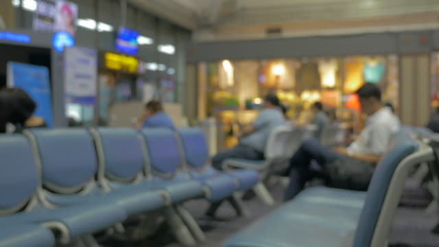 blurred people sitting waiting at terminal airport station - аэровокзал стоковые видео и кадры b-roll