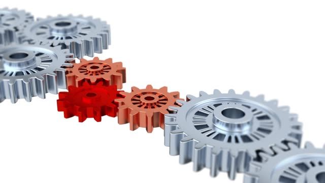 Blurred Silver Gears with One Red Turning in the middle