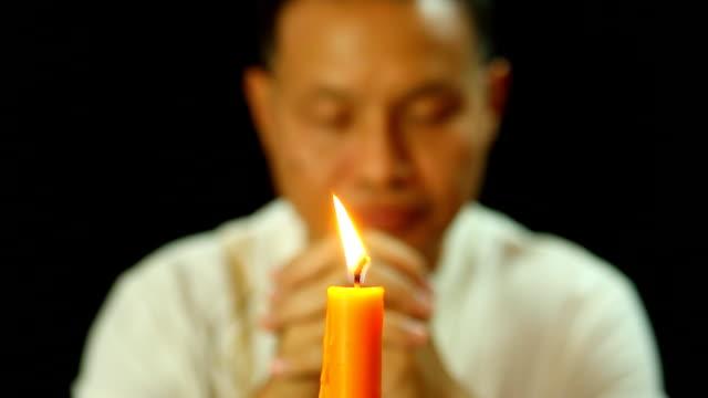 stockvideo's en b-roll-footage met wazig thaise man bidden met zwarte achtergrond - heilig geschrift
