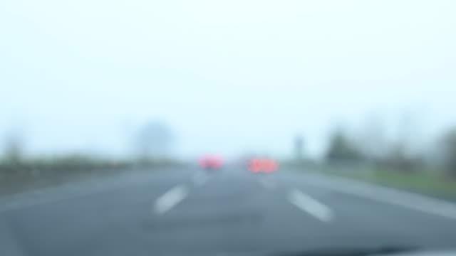 stockvideo's en b-roll-footage met wazig video van een auto reizen op een snelweg tijdens een bewolkte en regenachtige dag. - mist donker auto