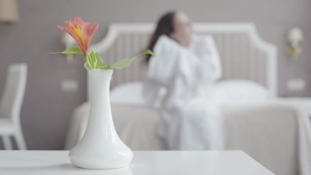 Blurred woman wiping wet hair with towel in hotel room. Vase with flower standing at the foreground. Unrecognizable female tourist resting after shower in accommodations at resort. Tourism, leisure.