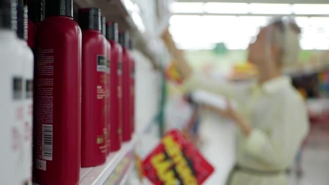 giovane donna sfocata che sceglie balsamo per capelli o shampoo in un negozio di bellezza. donna in possesso di un prodotto per la cura del corpo - mercanzia video stock e b–roll