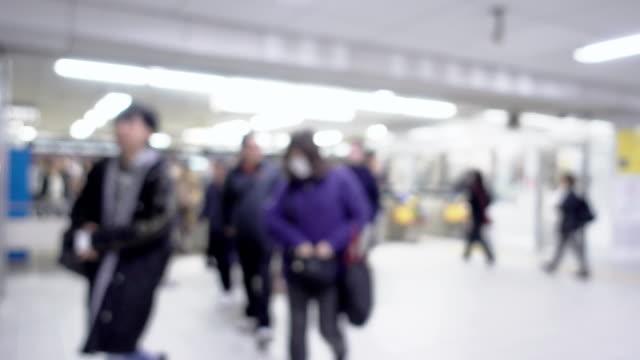 sfocato con la folla che cammina passa il cancello automatico nella stazione ferroviaria - fare video stock e b–roll