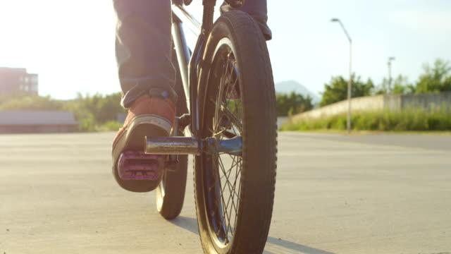 SLOW MOTION CLOSE UP: Bmx biker doing cool jumping tricks over the sunset sun video