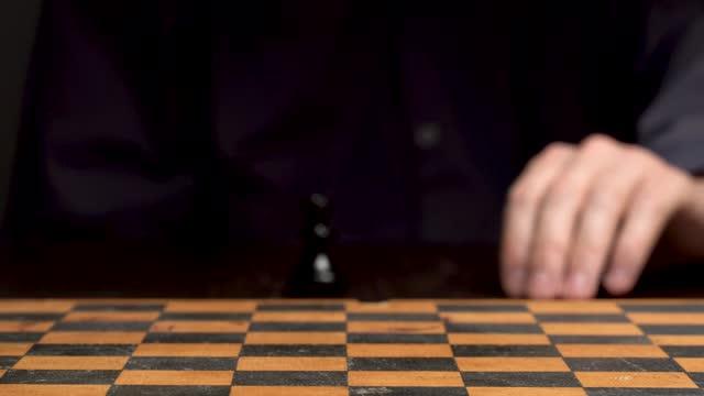 brettspiel schach. der spieler schneidet figuren im schach. sportstrategie und glücksspiel. der spieler ist ein mann an einem tisch in einem dunklen schlüssel. ein mann im hemd an einem glücksspieltisch. - könig schachfigur stock-videos und b-roll-filmmaterial