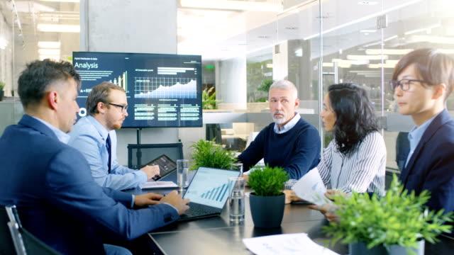 board of directors hat jahrestagung, heterogene gruppe von geschäftsleuten in der modernen konferenzraum diskutieren statistiken und arbeitsergebnisse. im hintergrund projektor zeigt unternehmen wachstum. - konferenzraum videos stock-videos und b-roll-filmmaterial