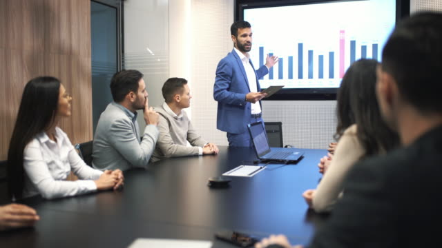 Board room meeting. Closeup of a board room meeting at a business company, usual scene at any modern company. There are five men and three woman, one of the men is speaking in front of a large screen that's showing monthly revenue of their company. 4k dolly shot. accounting stock videos & royalty-free footage