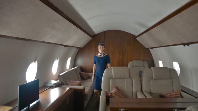 Board stewardess check private jet salon and walk to camera Board stewardess check private jet salon and walk to camera with invite and meet passengers. Luxury life concept. private airplane stock videos & royalty-free footage