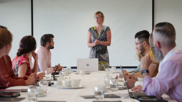 Boardroom Smiles A group of work colleagues in the board room with a woman with glasses leads the discussions. guidance stock videos & royalty-free footage