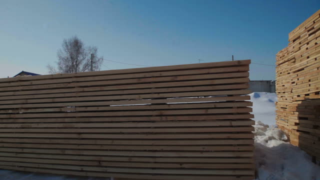 Boards for building standing on the street on a background of blue sky and white snow video