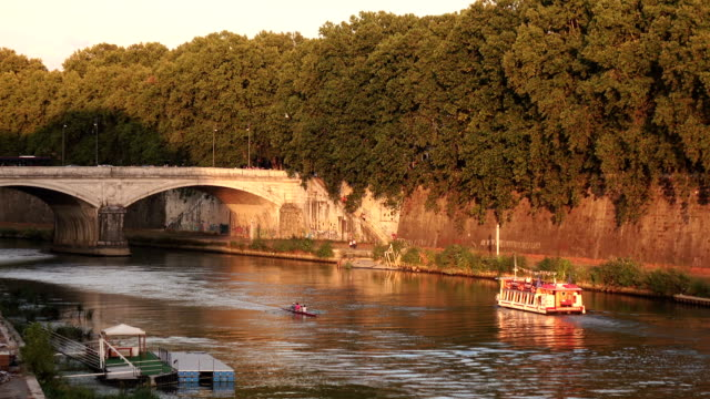 Boat and the canoe floating on the river near the bridge surrounded by green trees video