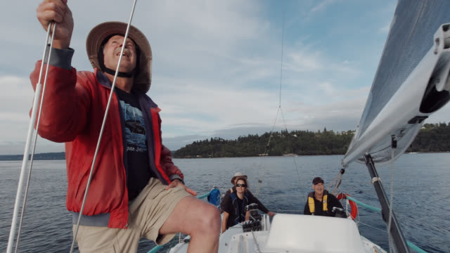 A Boat Captain in His Sixties and His Crew Watch the Jib of a Sailboat in Puget Sound near Seattle, Washington