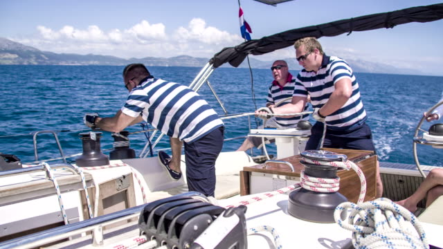 MS Boat Crew On A Sailboat HD1080p: MEDIUM shot of two men tights a rope around a winch while other boat crew is behind them on a deck of a sailboat. Also available in 4K resolution. regatta stock videos & royalty-free footage
