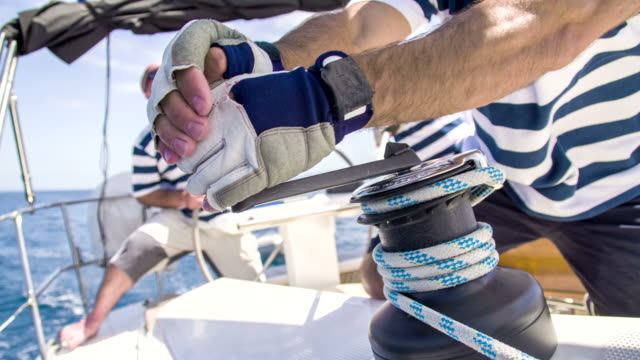 CU TU Boat Crew Tightening The Sail HD1080p: CLOSE-UP TILT UP shot of a man tights a rope around a winch with a winch handle while other boat crew behind him navigating a sailboat. Also available in 4K resolution. sail stock videos & royalty-free footage