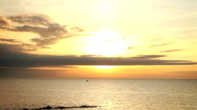Boat drives past cinematic orange sunset at dusk near Cleveland Ohio video