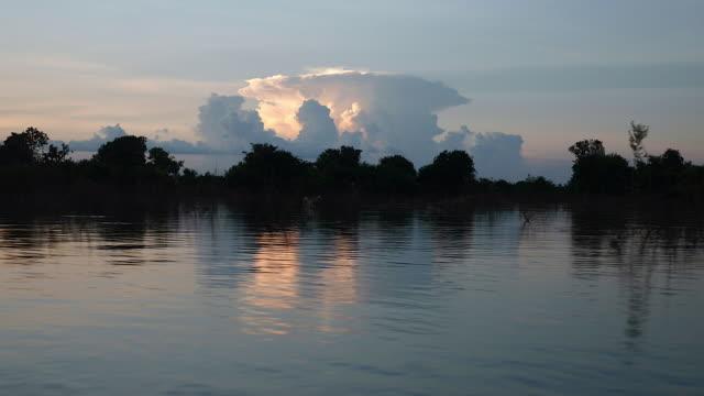 vidéos et rushes de pendant une balade en bateau sur un lac avec cloud formation contre le coucher de soleil - lac reflection lake