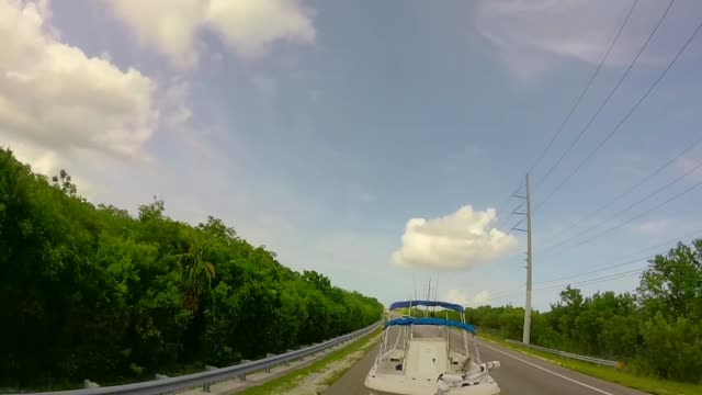boat getting towed behind truck driving on us 1 through the florida keys - rimorchiatore video stock e b–roll