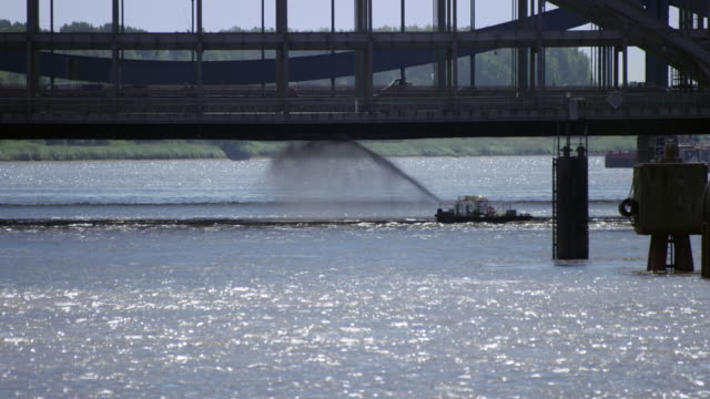 Boat is cleaning a bridge from underneath with a water jet video