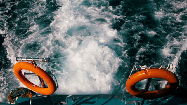 boat is floating on the waves and leaves a trail in the red sea. slow motion - nastro per capelli video stock e b–roll