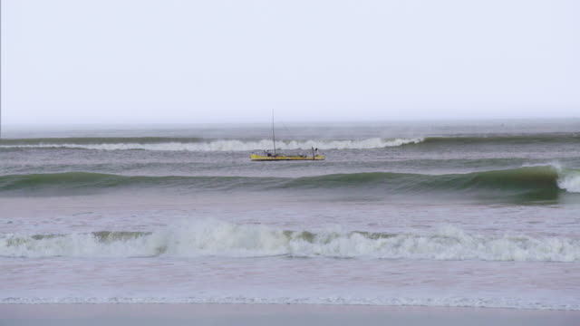 Boat moving along the coast. High waves