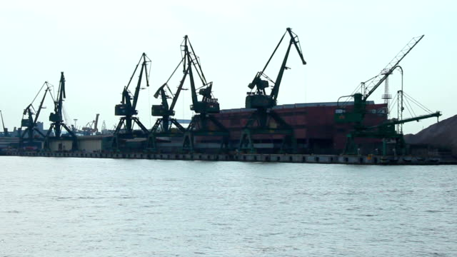 Boat moving by seaside port cranes and storehouses, freight transportation video
