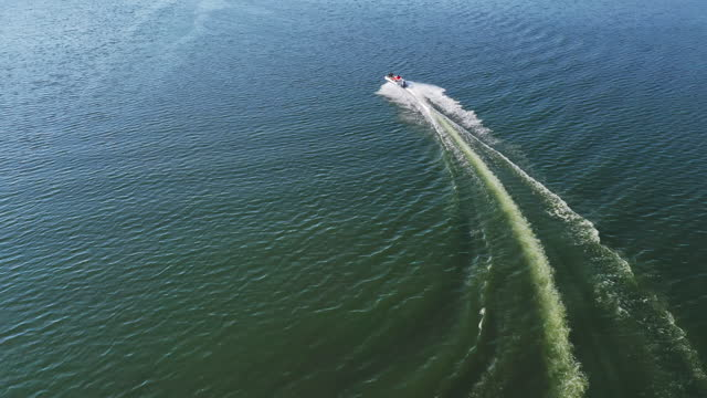 Boat near the big bridge. Motor boat floating on blue water of a beautiful river. Motion of boat on water surface. Aerial view.
