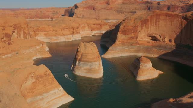 aerial boat in sella a un butte al reflection canyon, lago powell - riserva naturale parco nazionale video stock e b–roll