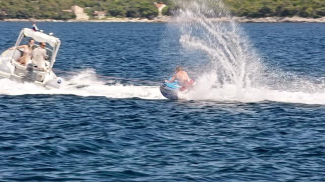 stockvideo's en b-roll-footage met slo mo boot caravan een persoon op een opblaasbare buis op zee - opblaasband
