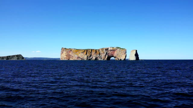 boat view of rocher perce rock in gaspe peninsula, quebec, gaspesie region with dark blue water - penisola video stock e b–roll