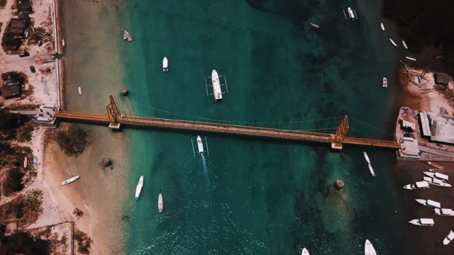 Boats Passing Under The Yellow Bridge Of Nusa Ceningan In Bali With Crystal Clear Water 4K video