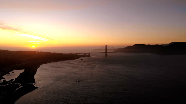 boats sailing into sunset. beautiful aerial over the ocean and golden bridge in California in twilight.