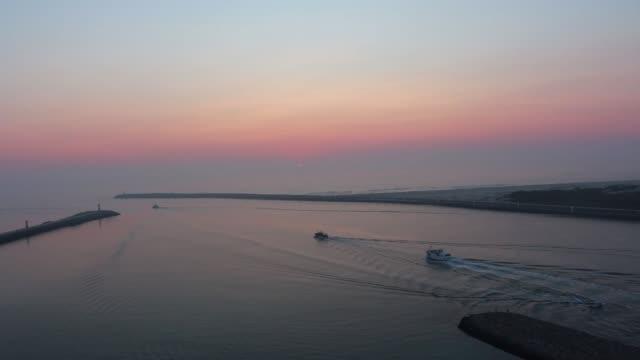 vídeos de stock e filmes b-roll de boats slowly leaving the harbor and sailing into the horizon in peaceful ocean. - aveiro