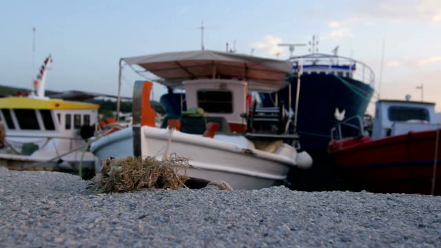 Boats with fishing equipment are tied with ropes for the pier, wharf video